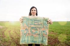 Glimlachende vrouw die eco vriendschappelijke zak met Kringloop gedrukte teksten tonen Royalty-vrije Stock Foto