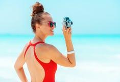 Glimlachende vrouw die foto's met retro fotocamera nemen op zeekust stock foto's
