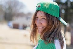 Glimlachende vrouw die groene achterwaartse snapback honkbalhoed dragen royalty-vrije stock afbeelding
