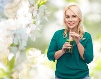 Glimlachende vrouw die groentesap drinken of smoothie stock fotografie