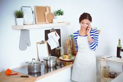 Glimlachende vrouw die haar cellphone in de keuken houden Glimlachende Vrouw Royalty-vrije Stock Afbeeldingen
