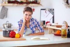 Glimlachende vrouw die haar cellphone in de keuken houden Glimlachende Vrouw Stock Afbeeldingen