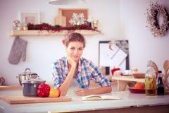Glimlachende vrouw die haar cellphone in de keuken houden Glimlachende Vrouw Stock Foto's