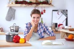 Glimlachende vrouw die haar cellphone in de keuken houden Glimlachende Vrouw Stock Afbeelding