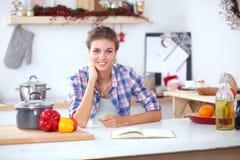Glimlachende vrouw die haar cellphone in de keuken houden Glimlachende Vrouw Stock Foto