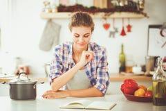 Glimlachende vrouw die haar cellphone in de keuken houden Glimlachende Vrouw Royalty-vrije Stock Fotografie