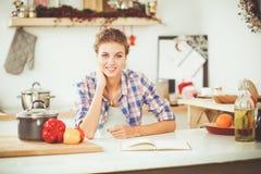 Glimlachende vrouw die haar cellphone in de keuken houden Glimlachende Vrouw Royalty-vrije Stock Foto's