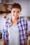 Glimlachende vrouw die haar cellphone in de keuken houden Glimlachende Vrouw Stock Fotografie