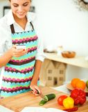 Glimlachende vrouw die haar cellphone in de keuken houden Stock Foto