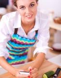 Glimlachende vrouw die haar cellphone in de keuken houden Royalty-vrije Stock Afbeelding
