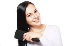 Glimlachende vrouw die haar haar borstelen Royalty-vrije Stock Afbeelding