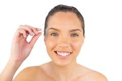 Glimlachende vrouw die haar pincet met behulp van Stock Foto's