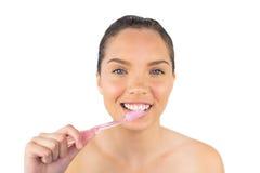 Glimlachende vrouw die haar tanden borstelen Stock Afbeeldingen
