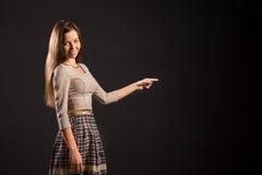 Glimlachende vrouw die haar vinger met exemplaarruimte richten Royalty-vrije Stock Foto