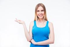 Glimlachende vrouw die iets op de palm voorstellen Stock Fotografie