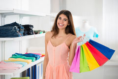 Glimlachende Vrouw die Kleurrijke het Winkelen Zakken in Kledingsopslag dragen stock fotografie