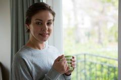 Glimlachende vrouw die kop van koffie hebben thuis stock afbeelding