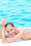 Glimlachende vrouw die kuuroordbehandeling naast pool neemt Stock Afbeeldingen