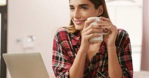 Glimlachende vrouw die laptop met behulp van terwijl het drinken van koffie stock video