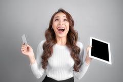 Glimlachende vrouw die lege de tabletpc van de creditcardgreep ter beschikking, over grijze achtergrond tonen royalty-vrije stock foto