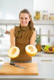 Glimlachende vrouw die meloenplakken in keuken tonen Royalty-vrije Stock Fotografie