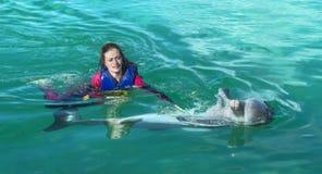 Glimlachende vrouw die met dolfijn in blauw water zwemmen stock foto's