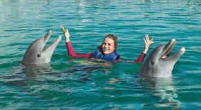 Glimlachende Vrouw die met dolfijnen in blauw water zwemmen stock afbeelding