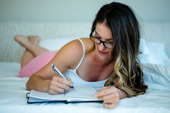 glimlachende vrouw die met glazen in een boek schrijven royalty-vrije stock foto