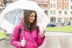 Glimlachende vrouw die met paraplu haar cellphone in de straat kijken royalty-vrije stock afbeelding
