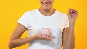 Glimlachende vrouw die muntstuk in spaarvarken, begroting, besparingen voor toekomstige investering zetten stock footage