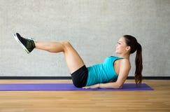 Glimlachende vrouw die oefeningen op mat in gymnastiek doen Royalty-vrije Stock Foto