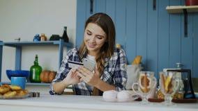Glimlachende vrouw die online het winkelen doen gebruikend smartphone en creditcard terwijl ontbijt thuis in de keuken hebben stock videobeelden