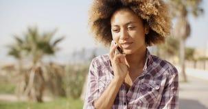 Glimlachende vrouw die op celtelefoon spreekt stock foto's