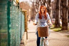 Glimlachende vrouw die op een fiets tijdens dag in stad genieten van Stock Afbeeldingen