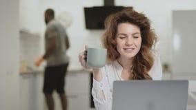 Glimlachende vrouw die op grappig nieuws op computer letten bij open keuken stock video