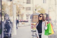Glimlachende vrouw die op het winkelvenster richten alvorens stor in te gaan Royalty-vrije Stock Fotografie