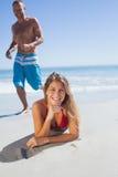 Glimlachende vrouw die op het zand liggen terwijl man die bij haar aansluiten zich Stock Afbeelding