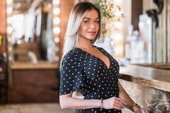 Glimlachende vrouw die op klanten wachten Zeer mooie sexy blondevrouw die camera met glimlach bekijken royalty-vrije stock foto