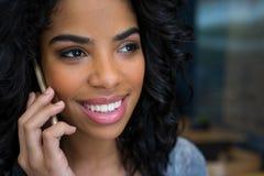 Glimlachende vrouw die op mobiele telefoon in koffiewinkel spreken Royalty-vrije Stock Foto