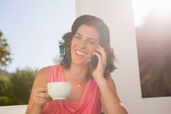 Glimlachende vrouw die op mobiele telefoon spreken terwijl het houden van koffiekop Royalty-vrije Stock Afbeeldingen