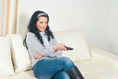 Glimlachende vrouw die op TV let Royalty-vrije Stock Afbeeldingen