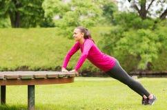 Glimlachende vrouw die opdrukoefeningen op bank in openlucht doen Stock Afbeeldingen