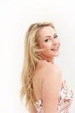 Glimlachende vrouw die over haar schouder kijkt Stock Foto