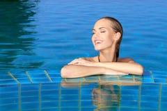 Glimlachende Vrouw die in Pool wordt weerspiegeld royalty-vrije stock fotografie