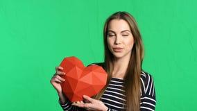 Glimlachende vrouw die rode veelhoekige document hartvorm houden stock footage