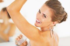 Glimlachende vrouw die roldeodorant op underarm in badkamers toepassen Royalty-vrije Stock Foto's