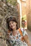 Glimlachende vrouw die tegen een muur leunen stock foto