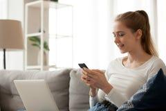 Glimlachende vrouw die telefoon, mobiel apparaat die app met behulp van, op bank zitten stock afbeeldingen