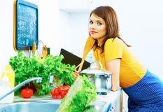 Glimlachende vrouw die thuis keuken koken Stock Foto's