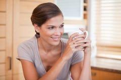 Glimlachende vrouw die van een kop van koffie geniet Stock Foto's